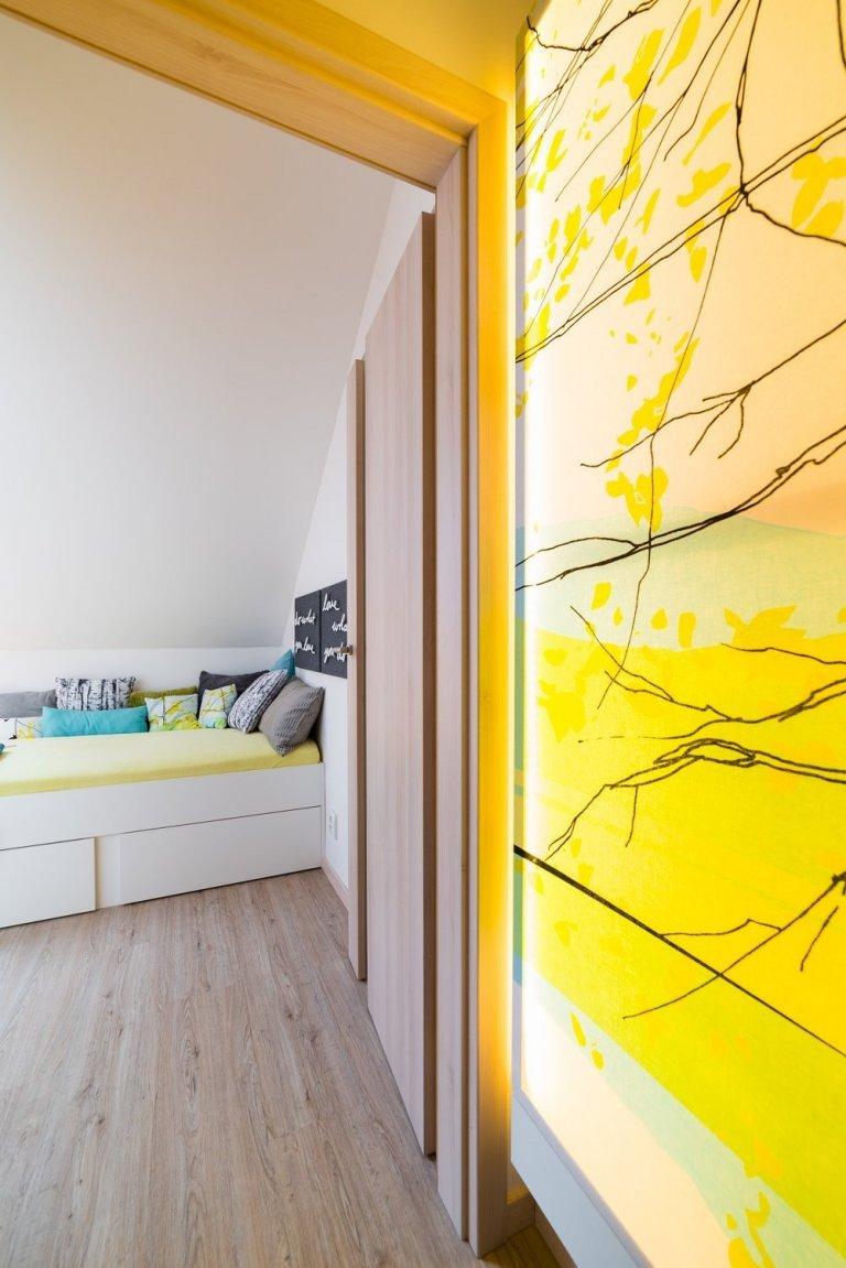 Multifiknční místnost v podkroví rodinného domu funguje jako šatna a pokoj pro hosty v jednom. Barevně navazuje na světelný obraz s přírodním motivem v chodbě.…