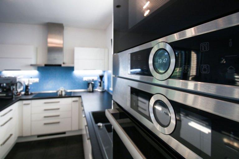Čistá prostorná kuchyně praktického tvaru U v moderní bílo-černo-modré kombinaci. Požadavkem byla velká pracovní plocha, místo na kávovar a barové sezení. Vše…