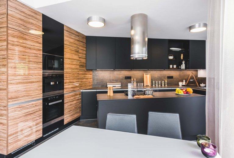 Luxusní tmavá dvířka Top Akryl Matt Black navazují na skříně s vysokým leskem v dřevěném dezénu Oliva, díky čemuž místnost získává neutuchající energii a…