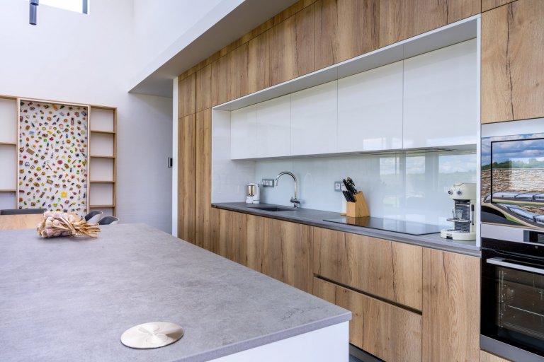 Velké dřevěné plochy sestavy působí čistě a romanticky, uprostřed jsou pak vystřídány mycím a varným centrem se skleněnou zástěnou, díky čemuž je prostor hezky symetrický i příjemně členitý.