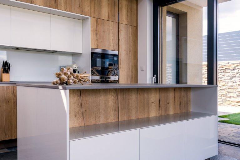 Kuchyňskou stěnu doplňuje, či spíše rozšiřuje také ostrůvek s šedou pracovní deskou v dekoru Dekton - Keon.