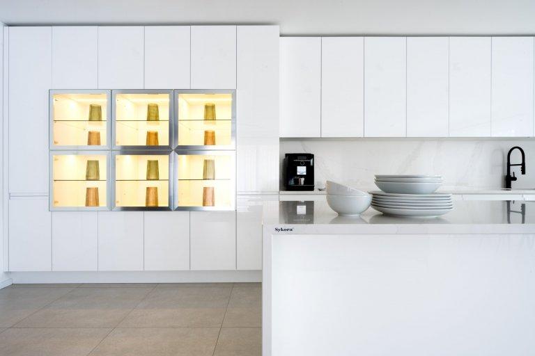 Specialitou sestavy, něčím, co originálně vybočuje z šablon, je prosklená vitrína v levé části vysokých skříní. Prosvětluje už tak jasný prostor, a díky vnitřnímu podsvícení mu dodává až magickou hladivost.