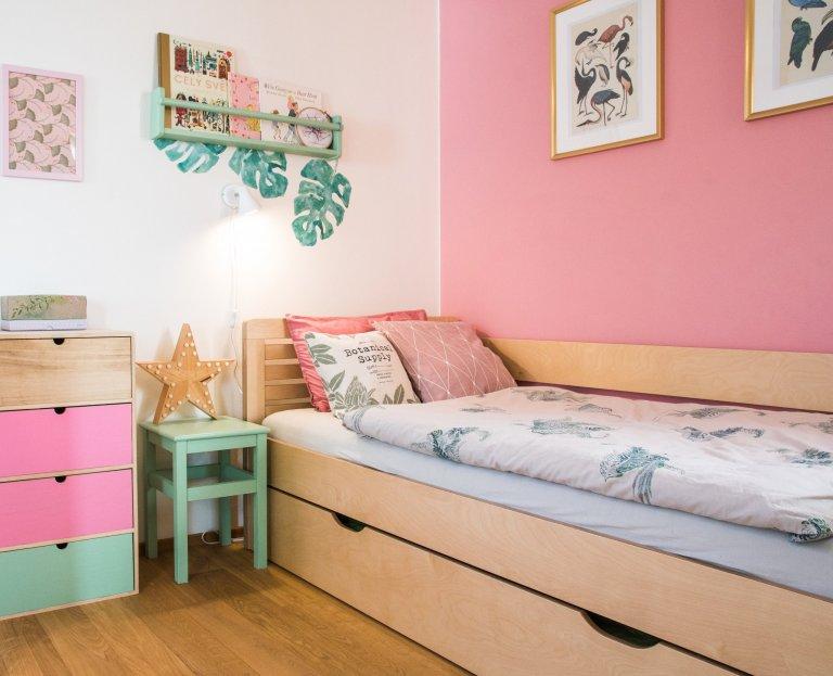 Návrh a realizace pokoje pro dvě holčičky. Pokoji dominuje oblíbená růžová barva na stěně, která je zjemněná zelenobílou tapetou a jemně zelenými doplňky.…