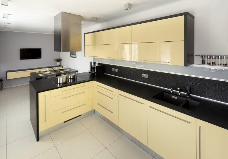 Impozantní moderní kuchyně v neobvyklé barevné kombinaci. Zářivě lesklé skříně ze světle žlutého lamina na první pohled krásně ladí smatně černým…