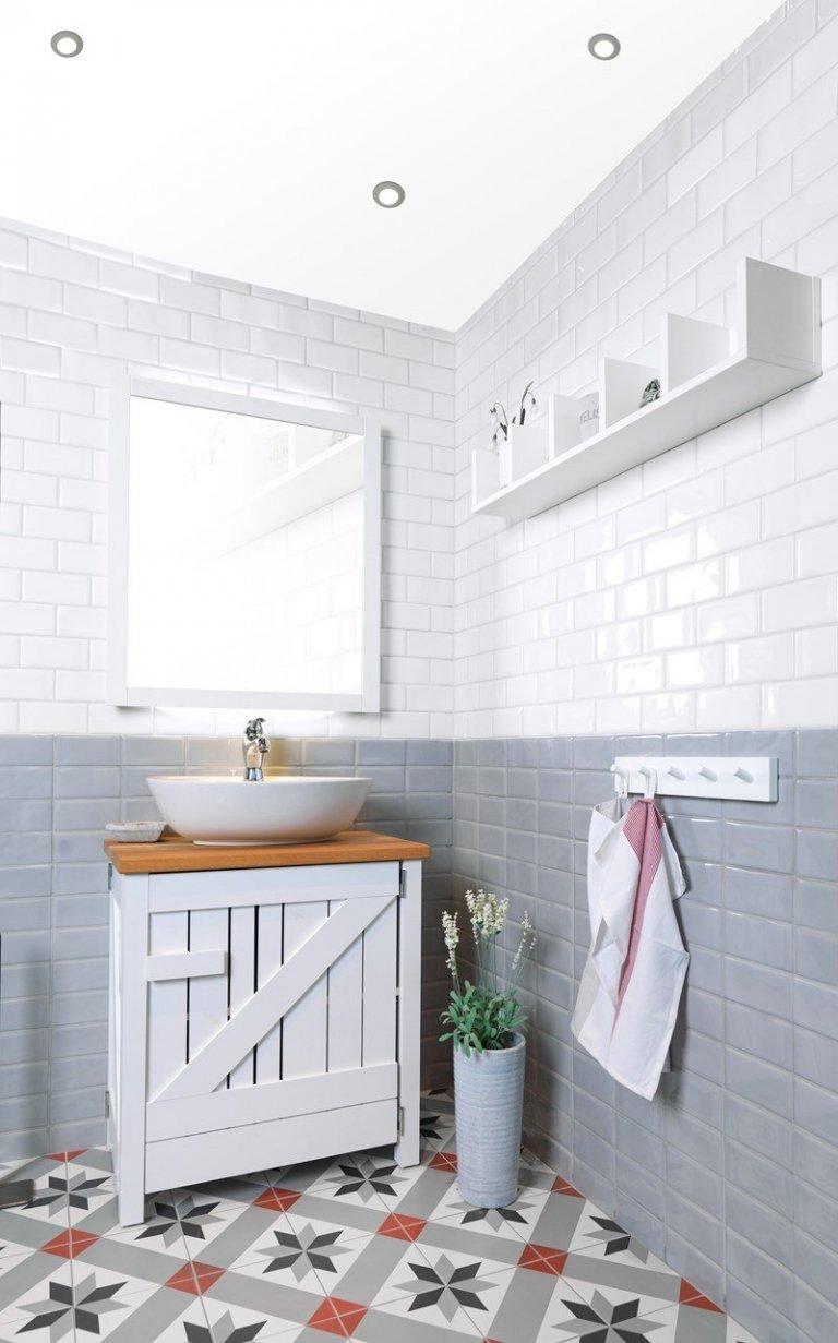 Retro koupelna s obdélníkovými obklady a dlažbou s klasickým historickým vzorem.