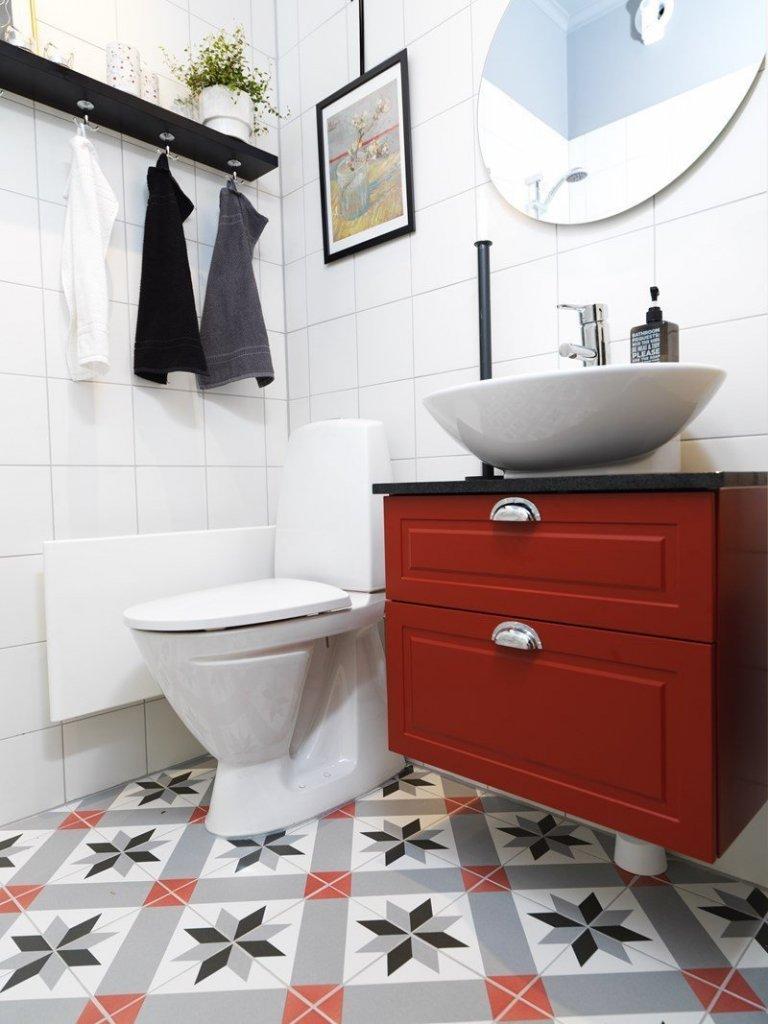 WC s bílými obklady a dlažbou s klasickým historickým vzorem.