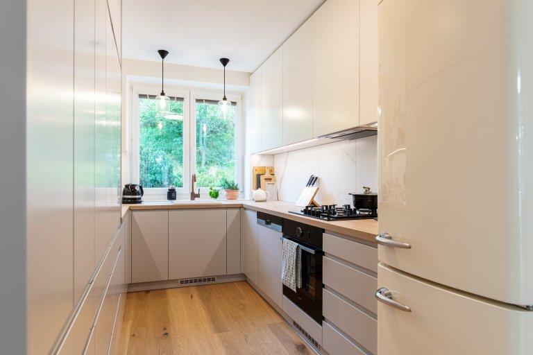 kuchyně v laku v kombinaci světle šedá a lomená bílá, samostatně stojící lednice