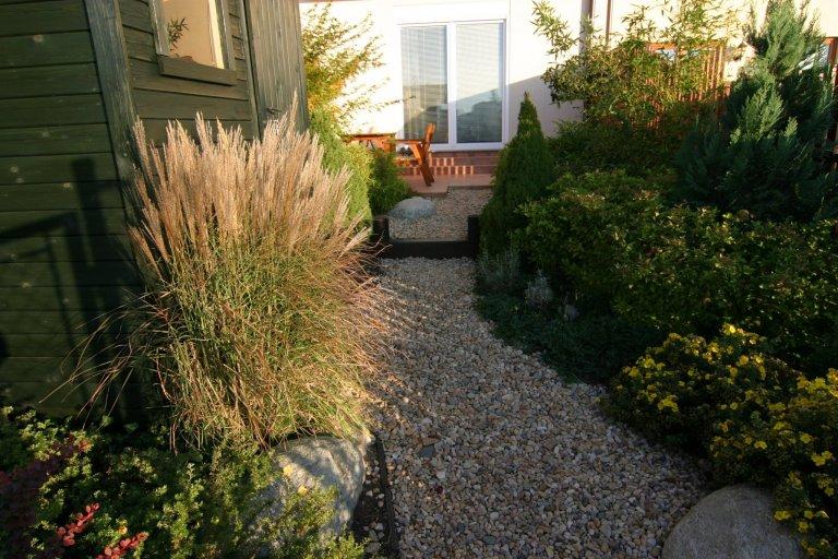 Jednoduchá zahrada u rodinného domku.  Svah na zahradě byl rozčleněn dřevěnými stupni. Zahrada skýtá dostatek soukromí, ačkoli je uprostřed linie…