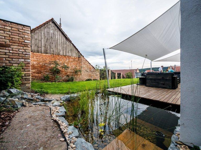 Se strohou kvádrovou hmotou domu ZEN HOME kontrastuje přírodní pojetí zahrady, její součástí je i koupací jezírko v těsné blízkosti domu a terasy.