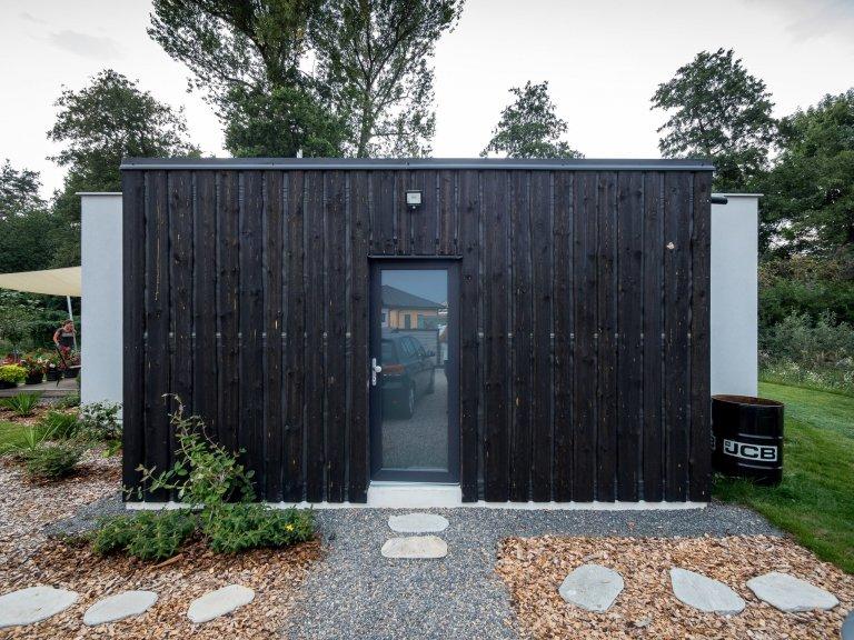 Základní hmotu domu ZEN HOME doplňuje přístavba z černých nesámovaných prken.