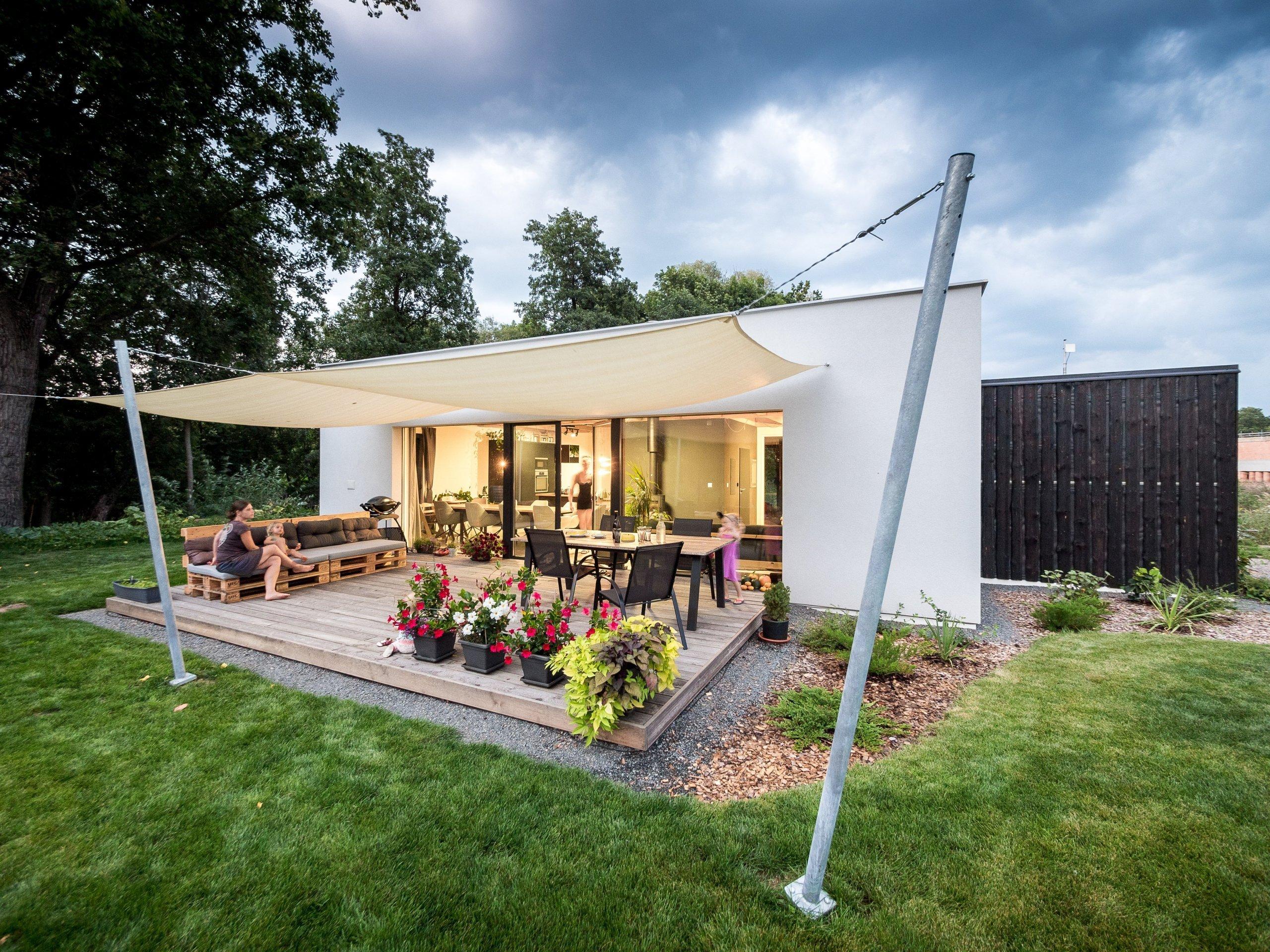 Základní hmotu domu ZEN HOME doplňuje přístavba z černých nesámovaných prken a výrazné textilní stínění terasy.